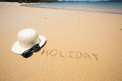Holiday written in the sand at the beach waves in the background Royalty Free Stock Photo