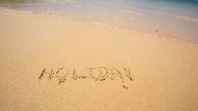 Holiday written in the sand at the beach waves in the background Royalty Free Stock Photography