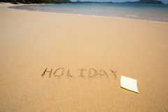 Holiday written in the sand at the beach waves in the background. And post it Stock Image