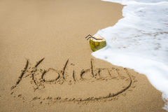 Holiday written in sand on a beach. The word Holiday written in the sand on a beach, with a coconut about to be washed away by an ocean wave Royalty Free Stock Images