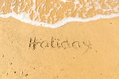 Holiday written on sand. Sandy beach with Holiday sign scribbled on beach sand. leisure time concept stock photography