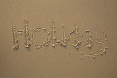 Holiday written in the sand. The text Holiday is written in the sand on the beach. This photograph was made at the last light of the day. The evening sun gives Stock Photo