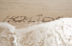 Holiday written in the sand. Washed by wave Royalty Free Stock Image