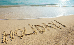Holiday - it is written on sand before a wave.  Stock Photo