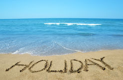 Holiday written on sandy beach Royalty Free Stock Images