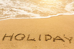 Holiday - written on sandy beach with the soft wave. Happy. Royalty Free Stock Images