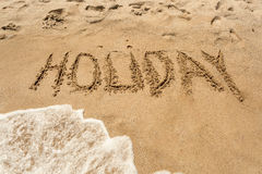 Holiday written on wet sand on the seashore. Word Holiday written on wet sand on the seashore Royalty Free Stock Images