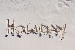 Holiday written on the white sand Royalty Free Stock Photos