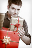 Holiday. Young man giving presents gifts boxes Stock Photography