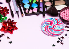 Holiday youth party makeup products. With brushes, lollipop, confetti and gift wrap bows. Selective focus, copy space Royalty Free Stock Image