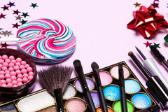 Holiday youth party makeup products. With brushes, lollipop, confetti and gift wrap bows. Selective focus, copy space Royalty Free Stock Images