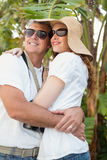 Holidaying couple hugging and smiling Stock Images