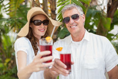 Holidaying couple toasting with cocktails Stock Images