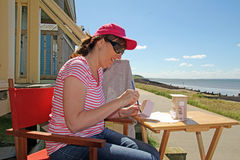 Holidaymaker crafting by sea Stock Images