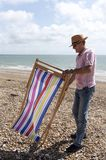 Holidaymaker erecting a deckchair on the beach. Elderly man in a straw hat erecting a deckchair on a pebble beach in southern England UK Royalty Free Stock Image