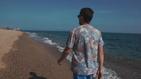Relaxed man is walking on sea pebble beach in sunny summer day, back view. Holidaymaker man is strolling along water line in seacoast in summer vacation. He is stock video footage