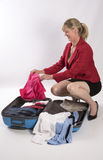 Holidaymaker packing a suitcase Stock Photography