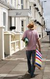 Holidaymaker som bara går med en deckchair arkivfoton