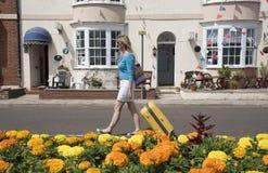Holidaymaker som går med den gula resväskan fotografering för bildbyråer