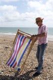 Holidaymaker som reser upp en deckchair på stranden royaltyfri bild