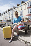 Holidaymaker with yellow suitcase and BB hotels Stock Image