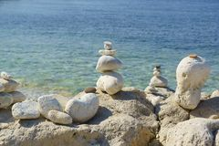 Holidaymakers on the beach resigned from the smooth stones of the pyramid. Balance Royalty Free Stock Photos