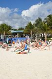Holidaymakers in keep fit exercise class on caribbean beach Royalty Free Stock Photo