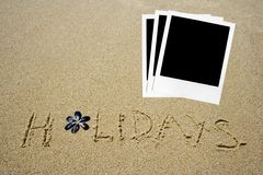 Holidays. Written in the sandy beach  with a group of polaroids photos Stock Photos