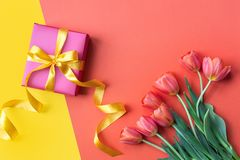 Holidays background. Gift box and flowers on orange desk. Copy space . Holidays background. Gift box and flowers on orange desk. Copy space royalty free stock image