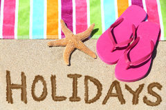 Holidays beach travel text. Concept. HOLIDAYS written in sand with water next to beach towel, summer sandals and starfish. Summer and sun vacation holidays Royalty Free Stock Photography