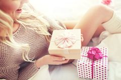 Close up of woman with birthday gifts in bed. Holidays, birthday, morning and people concept - close up of happy young woman gift boxes or presents in bed at Royalty Free Stock Photography