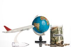 Holidays budget concept. Travel money savings in a glass jar with flying plane toy and world globe map on a white background, close-up Royalty Free Stock Photos