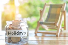 Holidays budget concept. Holidays money savings concept. Collecting money in the money jar for Holidays. Money jar with coins and. stock photo