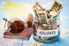 Holidays budget concept with passport and sunglasses. Holidays budget concept. Holidays money savings in a glass jar with passport and sunglasses on world map royalty free stock photos