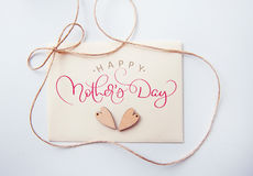Holidays card with wooden heart and text Happy mothers day. Calligraphy lettering hand draw stock image