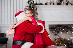 Holidays, celebration, childhood and people concept - smiling little girl hugging with santa claus over christmas tree Stock Photo