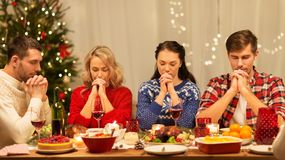 Friends praying before christmas dinner at home. Holidays and celebration concept - friends holding hands and praying before christmas dinner at home stock photo