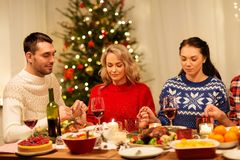 Friends praying before christmas dinner at home. Holidays and celebration concept - friends holding hands and praying before christmas dinner at home royalty free stock image