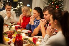 Friends having home christmas dinner and praying. Holidays and celebration concept - friends holding hands and praying while having christmas dinner at home royalty free stock image