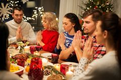 Friends having home christmas dinner and praying. Holidays and celebration concept - friends holding hands and praying while having christmas dinner at home stock images