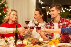 Happy friends drinking red wine at christmas party royalty free stock images