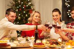 Happy friends drinking red wine at christmas party stock image