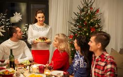 Happy friends having christmas dinner at home royalty free stock image