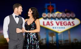 Happy couple at party over las vegas sign at night. Holidays, celebration and people concept - happy couple at party over welcome to fabulous las vegas sign Stock Photo