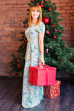 Holidays, celebration and people concept - smiling woman in dress holding red gift box over christmas tree background Royalty Free Stock Photos