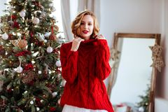 Smiling woman in red sweater over christmas tree background royalty free stock photography