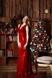 Holidays, celebration and people concept - young smiling woman in elegant red dress over christmas interior background Stock Photography
