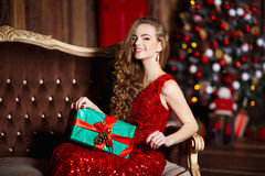 Holidays, celebration and people concept - young smiling woman in elegant red dress over christmas interior background Stock Images