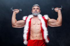 Holidays and celebrations, New year, Christmas, sports, bodybuilding, healthy lifestyle - Muscular handsome sexy Santa. Claus. on a black background with Royalty Free Stock Photos