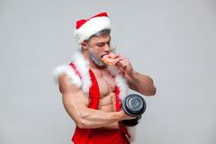 Holidays and celebrations, New year, Christmas, sports, bodybuilding, healthy lifestyle - Muscular handsome sexy Santa. Claus enjoys fresh baked piping hot Stock Photos